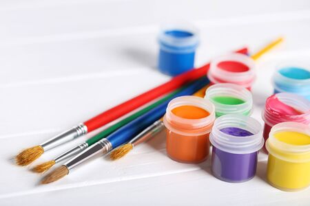 Colorful gouache paints and brushes on white wooden table Banco de Imagens - 138294066