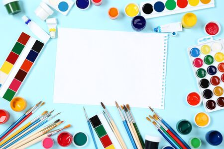 Colorful gouache paints with brushes and blank sheet of paper on blue background Banco de Imagens - 138294383