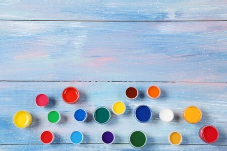 Colorful gouache paints on blue wooden table Banco de Imagens - 138296233