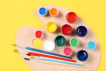 Colorful gouache paints with brushes and palette on yellow background Banco de Imagens - 138294266