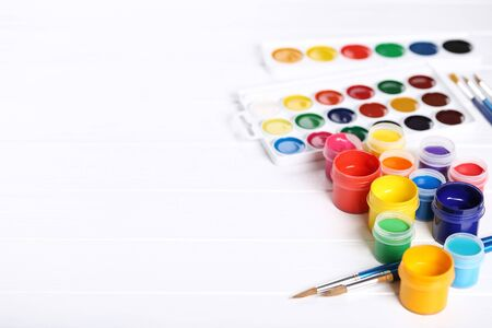 Colorful gouache paints and brushes on white wooden table Banco de Imagens