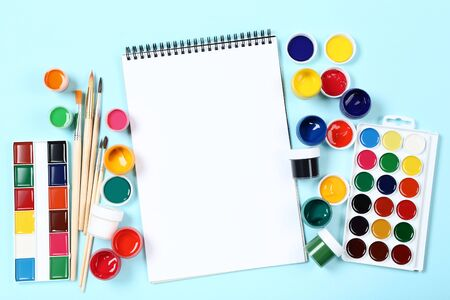 Colorful gouache paints with brushes and blank sheet of paper on blue background Banco de Imagens - 138296397
