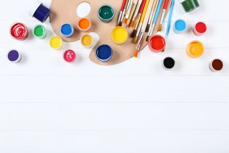 Colorful gouache paints and brushes on white wooden table Banco de Imagens - 138296402