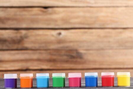 Colorful gouache paints on brown wooden background Banco de Imagens - 138296412