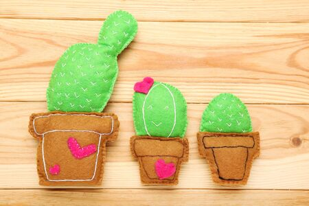 Different soft toy of cactuses on brown wooden table