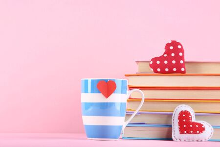 Fabric hearts with cup and stack of books on pink background