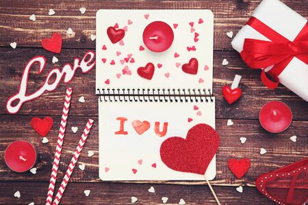 Valentine hearts with candles, notepad and text I Love You on wooden table