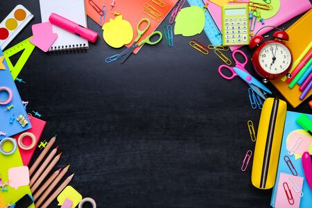 Different school supplies on blackboard Standard-Bild