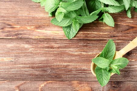 Mint leafs with spoon on brown wooden table