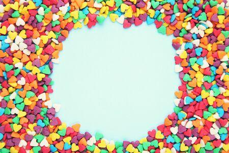 Chispitas en forma de corazón de colores sobre fondo azul. Foto de archivo