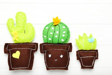 Different soft toy of cactuses on white wooden table
