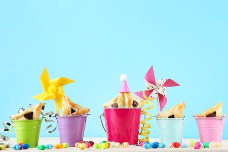 Purim vakantie samenstelling. Koekjes met emmers en feestartikelen op blauwe achtergrond