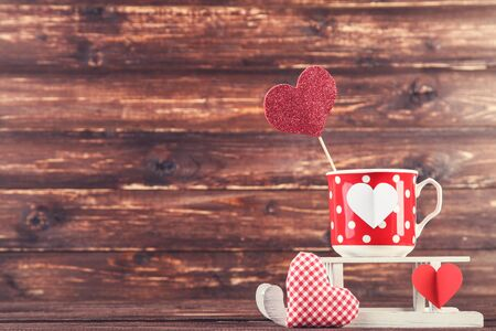 Fabric and paper hearts with cup and white sleigh on brown wooden table