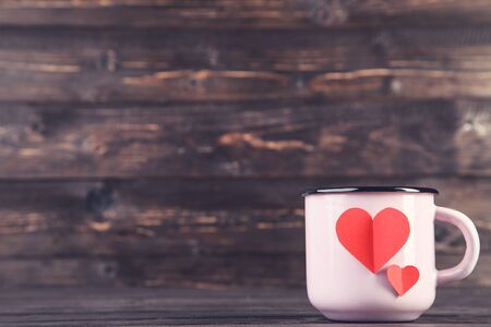 Paper hearts with mug on brown wooden table