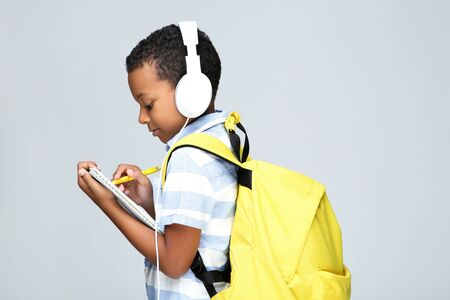 Young African American school boy writing in notepad with headphones and backpack on grey background