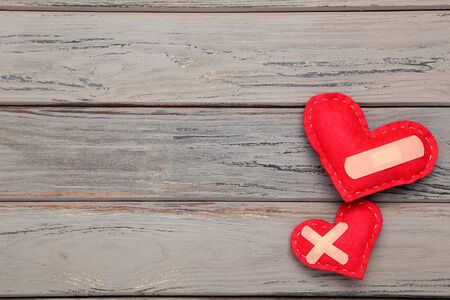 Red fabric hearts with bandage on wooden table Stock Photo