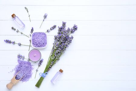 Lavender flowers with oil in bottles and salt on white wooden table