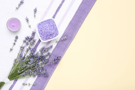 Lavender flowers with spa salt and candle on beige background