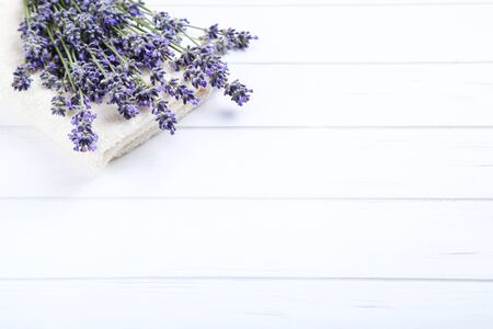 Lavender flowers with towel on white wooden table
