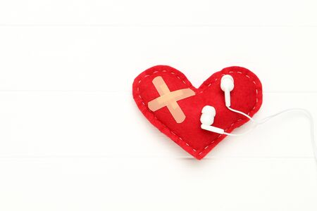 Red fabric heart with bandage and earphones on white wooden table Stock Photo