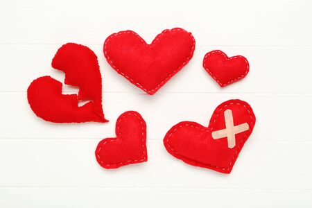 Red fabric hearts and bandage on white wooden table Stock Photo