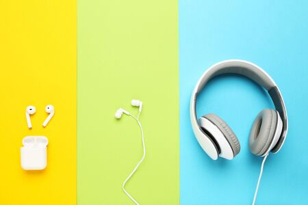 Three different earphones on colorful paper background Stockfoto