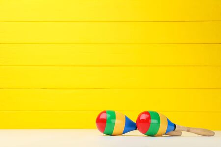Mexican maracas on yellow wooden
