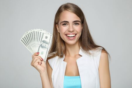Beautiful woman holding dollar banknotes on grey background