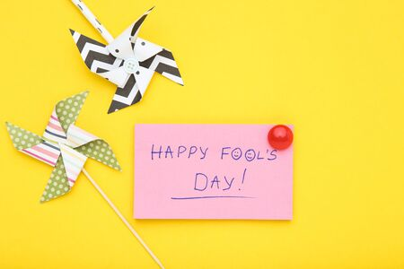 Text Happy Fool's Day with paper windmills on yellow background