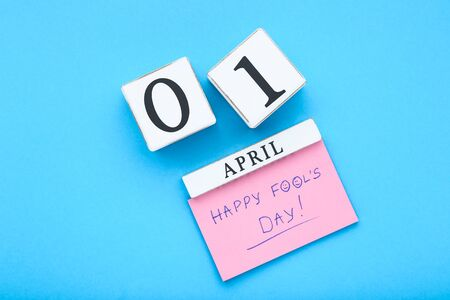 Text Happy Fool's Day with wooden calendar on blue background