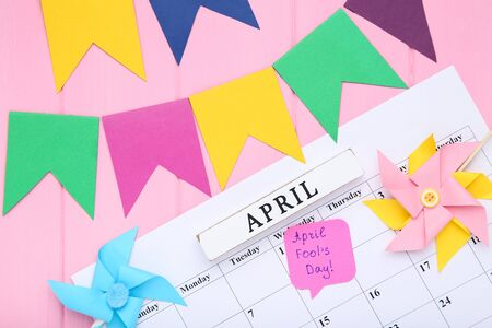 Text April Fool's Day on calendar with paper flags and windmills