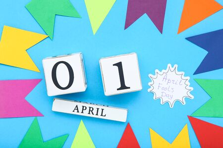 Text April Fool's Day with wooden calendar and paper flags on blue background