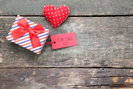 Text For Dad with gift box and red fabric heart on wooden table