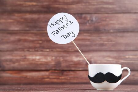 Text Happy Fathers Day and white cup with paper mustache on wooden table 版權商用圖片