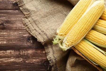 Ripe corn on brown wooden table