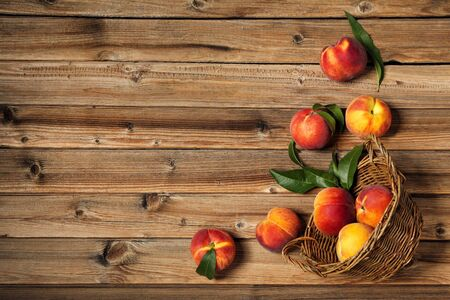 Fresh peaches with green leafs in basket on brown wooden table Standard-Bild