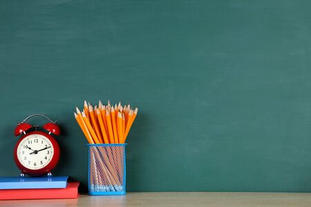 School supplies with red alarm clock on green background