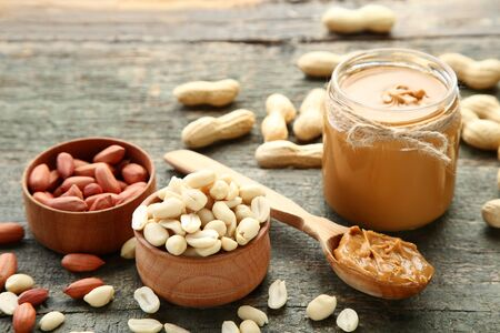 Peanut butter and nuts on grey wooden table Stock fotó