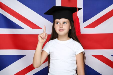 Young beautiful girl in graduation cap pointing by finger on british flag background