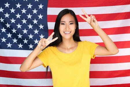 Junge Frau auf amerikanischem Flaggenhintergrund Standard-Bild