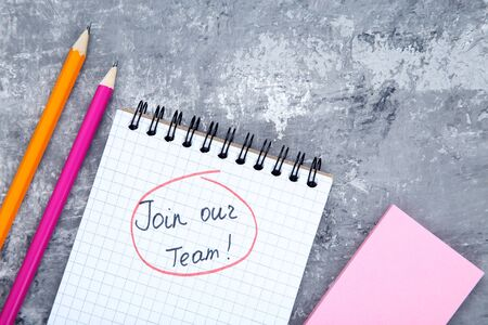 Text Join Our Team in notepad with pencils on grey background