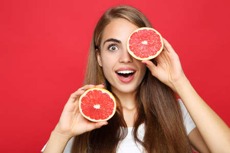 Young girl with fresh grapefruit on red background Banque d'images