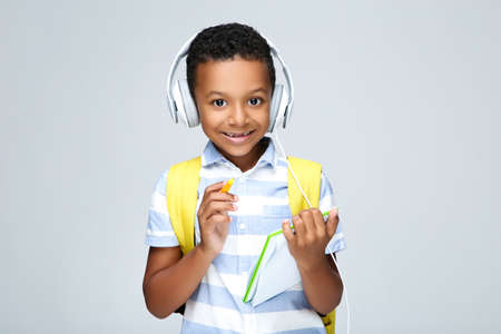Young African American school boy writing in notepad with headphones and backpack on gray background 스톡 콘텐츠