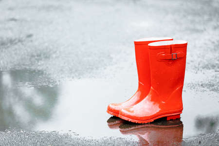 Red rubber boots in puddle after rain Stock Photo