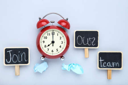 Text Join Our Team on black chalkboards with crumpled papers and alarm clock