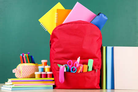 Backpack with school supplies on chalkboard background