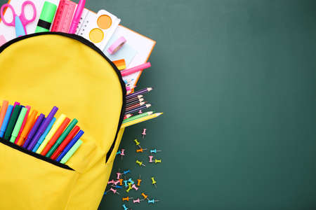 Backpack with school supplies on green background Zdjęcie Seryjne