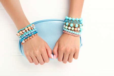 Female hands with bracelets holding handbag on white wooden background