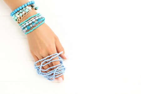 Female hand with blue bracelets on white wooden background