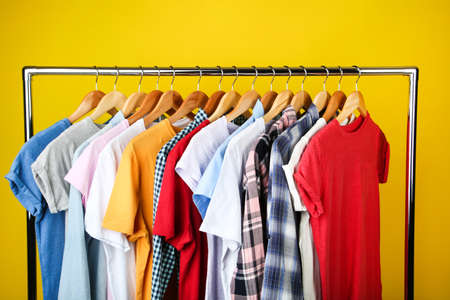 Wooden hangers with clothes on yellow background Banque d'images